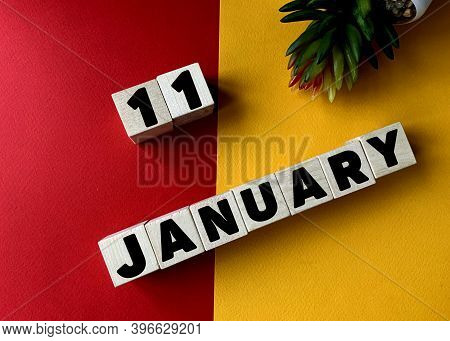 January 11 In Black Letters On Wooden Blocks On A Divided Yellow-red Background .next To A Flower .c