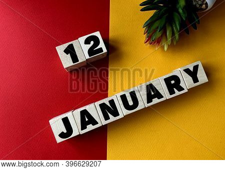 January 12 In Black Letters On Wooden Blocks On A Divided Yellow-red Background .next To A Flower .c