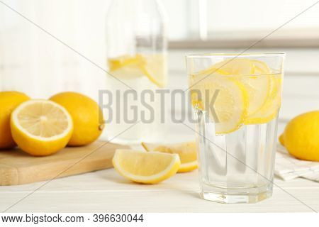 Soda Water With Lemon Slices And Fresh Fruits On White Wooden Table In Kitchen. Space For Text