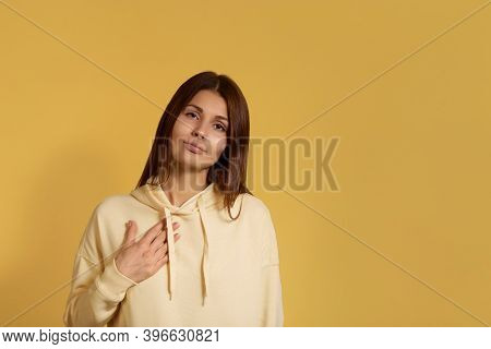 Young Caucasian Woman In A Yellow Hoodie Keeps Palm On Chest, Being Touched By Heartwarming Words, F