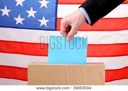 Hand with voting ballot and box on Flag of USA