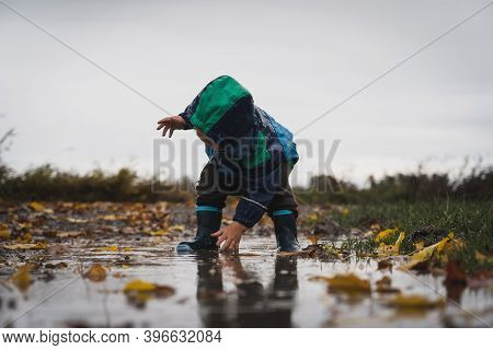 Cute Little Child Playing In The Puddle During Rain. Happiness And Pure Bliss, Not A Single Care In