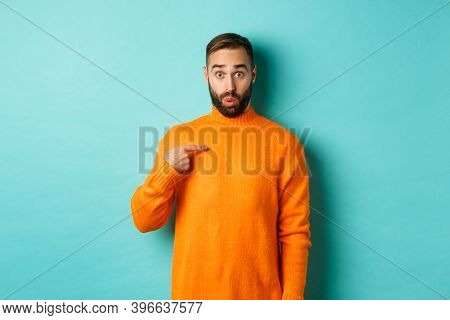 Man Pointing At Himself With Surprise Face, Being Chosen, Standing Confused Against Light Blue Backg