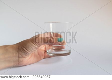 Hand Holding An Empty Glass On White Background
