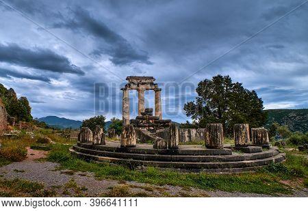 Ruins Of Tholos Of Ancient Greek Goddess Athena Pronaia In Delphi, Greece. Circle Of Parts And Resto