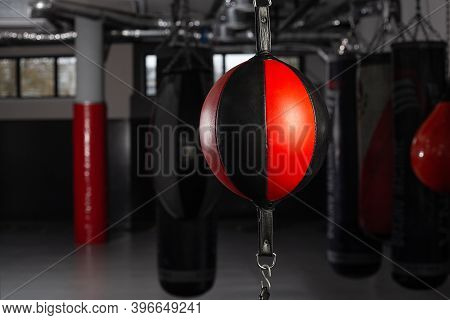 Round Black-red Punching Bag In The Boxing Gym On A Dark Background. Punching Red Punching Bag Conce