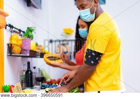 Young Couple Cooking In Kitchen With Protector Masks For Coronavirus. Friends While Cooking Healthy