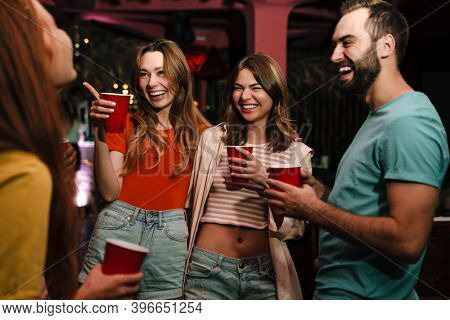 Group of happy young friends celebrating in the nightclub, dancing, drinking