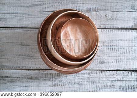 Stack Of Wooden Dishes Of Different Diameters From Elm On Wooden Background