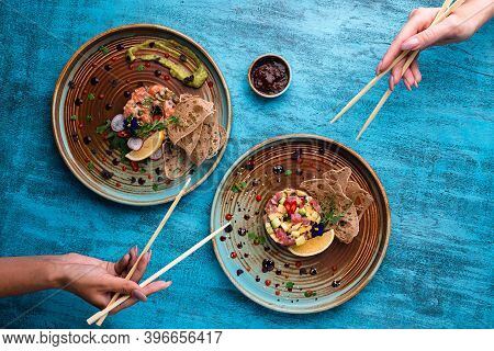 Young Woman Eats Salmon Tartare In A Restaurant. Health Food. Top View Of A Womans Hand Eats Salmon