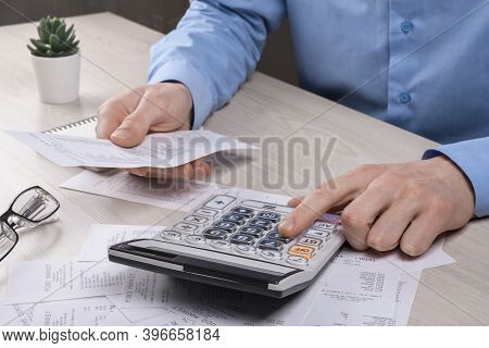Unrecognizable Businessman Using Calculator On Desk Office And Writing Make Note With Calculate Abou