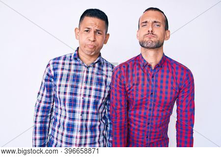 Young gay couple of two men wearing casual clothes puffing cheeks with funny face. mouth inflated with air, crazy expression.
