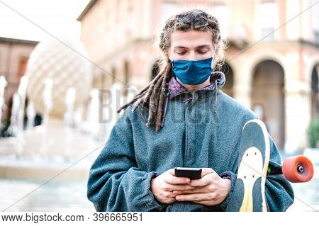 Unhappy Guy With Protective Mask Using Tracking App On Mobile Smartphone - Young Worried Millenial S