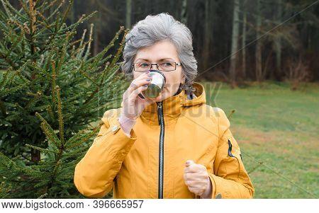 Elderly Woman Drinking Hot Tea In The Woods Outdoors. Portrait Of A Senior Woman Walking In Cold Wea