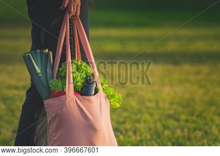 Woman Holding Pink Eco Friendly Reusable Shopping Bag With Fresh Bio Vegetables. Healthy Food Shoppi