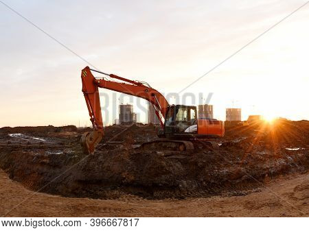 Excavator On Earthworks At Construction Site On Sunset Background. Backhoe On Foundation Work And Ro