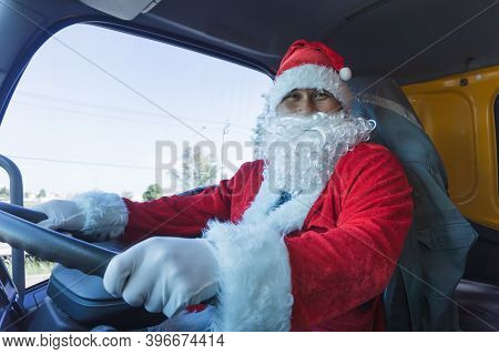 Uncle Santa Claus Driving A Car.truck Driver Wearing Santa Claus And Smiling Happy On Christmas Day.