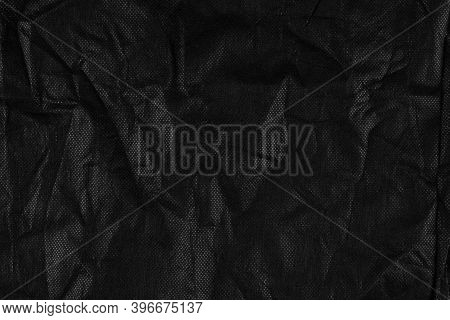 Background With Black Crumpled Sheet Of Fabric With Vignetting