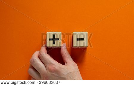 Plus Or Minus. Businessman Holds A Cubes With Plus Icon. Wooden Cube With Minus Icon. Beautiful Oran