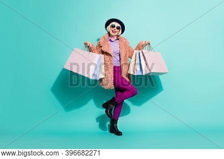 Photo Of Charming Senior Lady Wear Retro Jacket Headwear Eyeglasses Holding Bargains Isolated Teal C