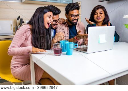 Indian Four People In Kitchen Looking At Laptop And Discussing A Homework Distance Learning