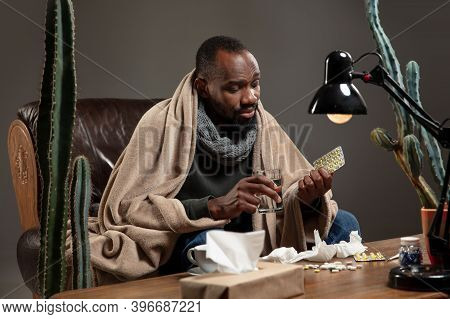 Cold And Flu. Young Man Wrapped In A Plaid Looks Sick, Ill, Sneezing And Coughing Sitting In Armchai