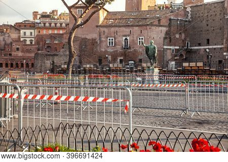 Road barriers with red-and-white warning tape blocking the Via dei Fori Imperiali road at Rome, Italy - lockdown due to Coronavirus COVID-19 pandemic outbreak concept