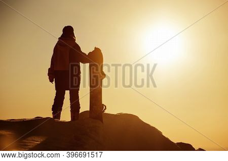 Girl Snowboarder Stands With Snowboard Against Sunset Sky. Ski Resort Concept