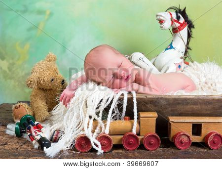 Newborn baby sleeping in a trench bowl surrounded by vintage antique toys