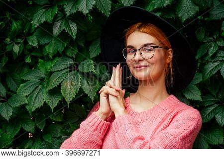 Smiling Redhead Outdoors Wear Pink Sweater And Black Hat In Green Leaves Background