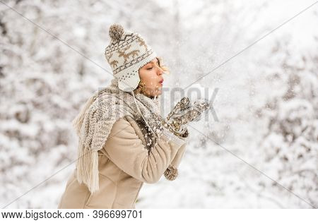 Blow Snowflakes Away. Happy Woman Blow Snow From Hands. Girl In Trendy Winter Coat. Girl Wear Warm M