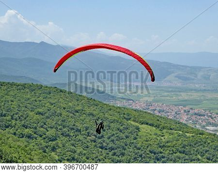 Paraglider Flying Red Wing From Brestovitsa In Bulgaria