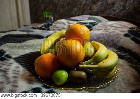 Fruit Plate On A Blanket With Oranges, Bananas, Kiwi, Pears, Lime, Kiwi Eat