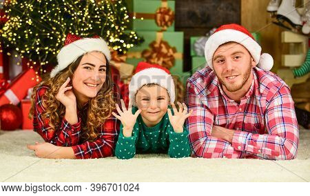 Winter Holidays. Parenthood Happiness. Christmas Tradition. Father Mother Little Son Christmas Tree