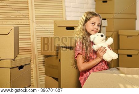 Excited About New House. Girl Child Play With Toy Near Boxes. Move Out Concept. Prepare For Moving.