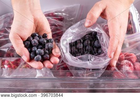 Frozen Blueberry In Hand, Closeup. Frozen Berries And Fruits In A Plastic Bag In Freezer