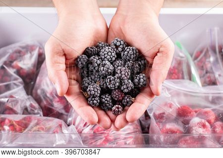 Frozen Blackberry In Hand, Closeup. Frozen Berries And Fruits In A Plastic Bag In Freezer