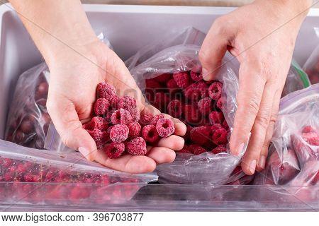 Frozen Raspberry In Hand, Closeup. Frozen Berries And Fruits In A Plastic Bag In Freezer