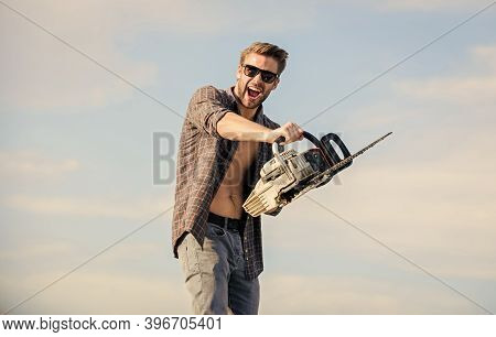 Handsome Man With Chainsaw Blue Sky Background. Gardener Lumberjack Equipment. Sharp Blade. Dangerou