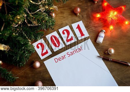 Letter Dear Santa On A Wooden Background With The Numbers 2021, A Blank Sheet Of Paper, Covid-19 Vac