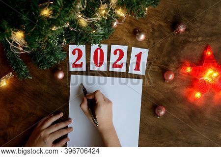 Woman's Hand Writes Wish List On A Wooden Background With The Numbers 2021, Sheet Of Paper And A Pen