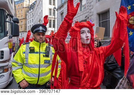 London, Uk - October 18, 2019: An Extinction Rebellion Red Brigade Protester Parading In Front Of A