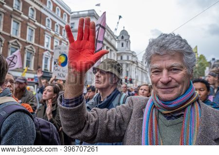 London, Uk - October 18, 2019: A Man Holds His Red Painted Hand Up While In A Group Of Extinction Re