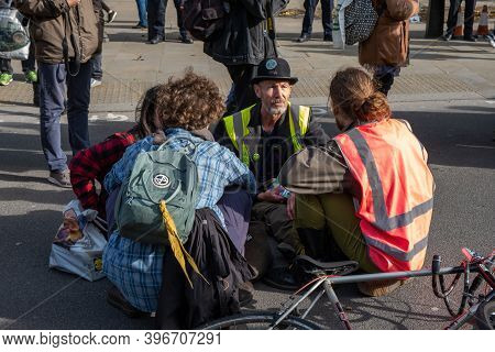 London, Uk - October 18, 2019: A Group Of Extinction Rebellion Protesters Sat In A Road Talking At A