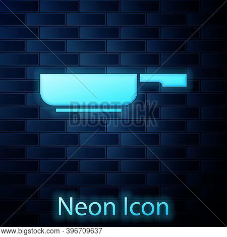 Glowing Neon Frying Pan Icon Isolated On Brick Wall Background. Fry Or Roast Food Symbol. Vector