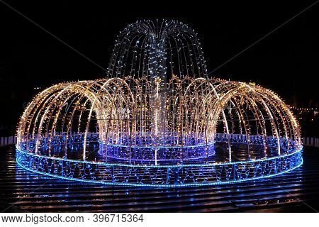 Beautiful Blue Lights In New Year Holidays In Night. Bright Fountain In Darkness. Artificial Fountai