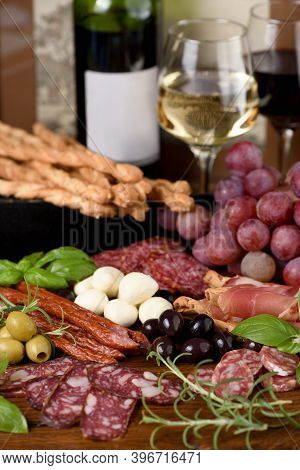 Antipasto. Dish With Sausage, Dried Ham, Salami, Crispy Grissini With Grapes. A Meat Appetizer Is A