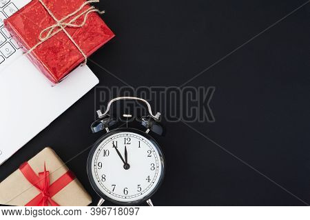 Top View Of Alarm Clock, Two Giftboxes And Laptop On Black Background, Copy Space For Text. Online S