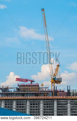 Moving Yellow Tower Cranes And Unfinished Building Construction Against Summer Cloudy Blue Sky. Buil