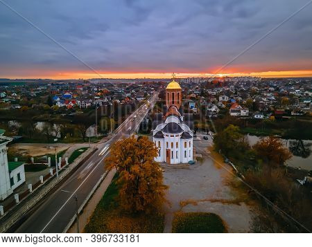 Hdr Aerial View Of Old Church Near River And Bridge In Small European City At Epic Sunset